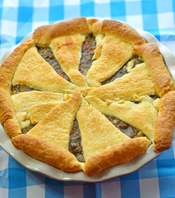 Whole baked beef pot pie sitting on the blue and white checkered background.