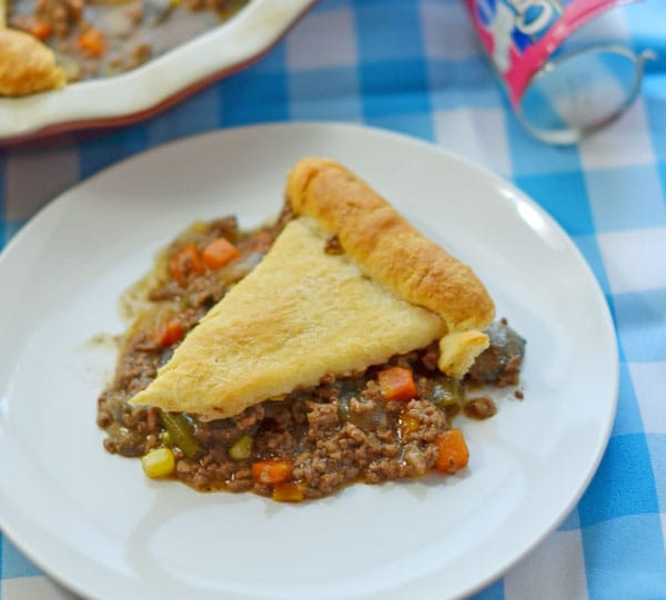 A slice of baked beef pot pie on a small round white plate on a blue and white checkerboard pattern background.