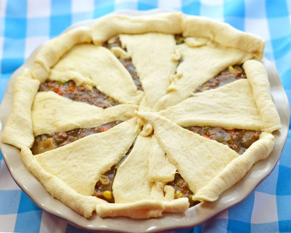 The whole unbaked beef pot pie in a ceramic red and white pie plate on a blue and white checkered background.
