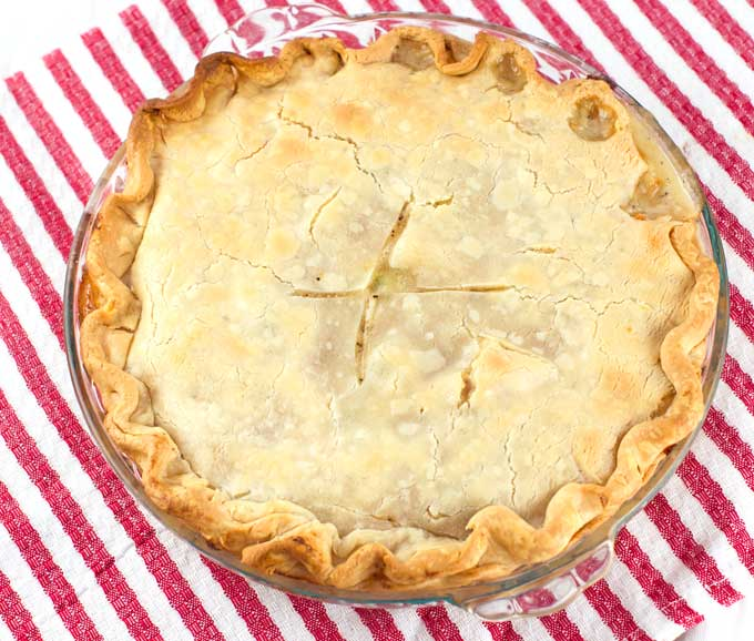 A whole baked chicken pot pie in a glass pie pan sitting on a red and white striped towel.