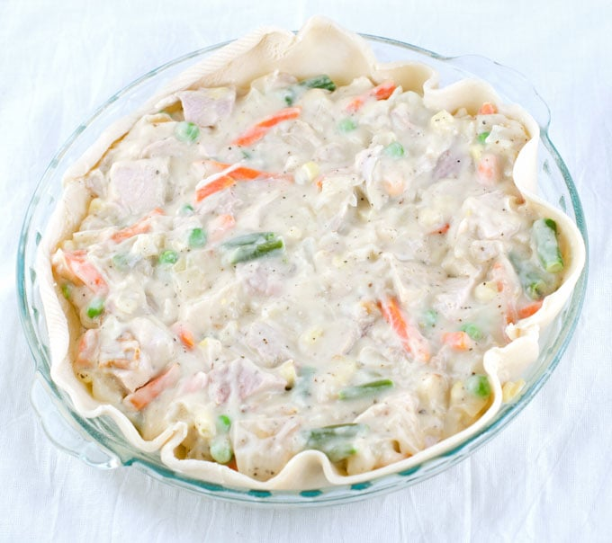 A whole unbaked chicken pot pie without the top crust in a glass pie pan with handles on a white cheesecloth background.