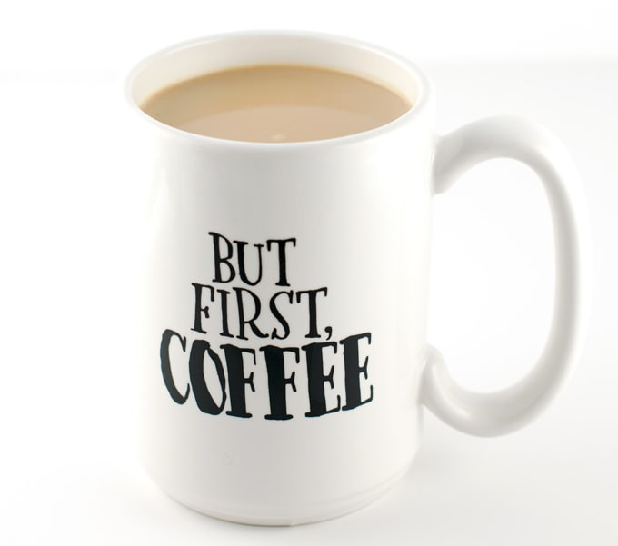 white coffee mug with words but first, coffee in black letters filled with coffee
