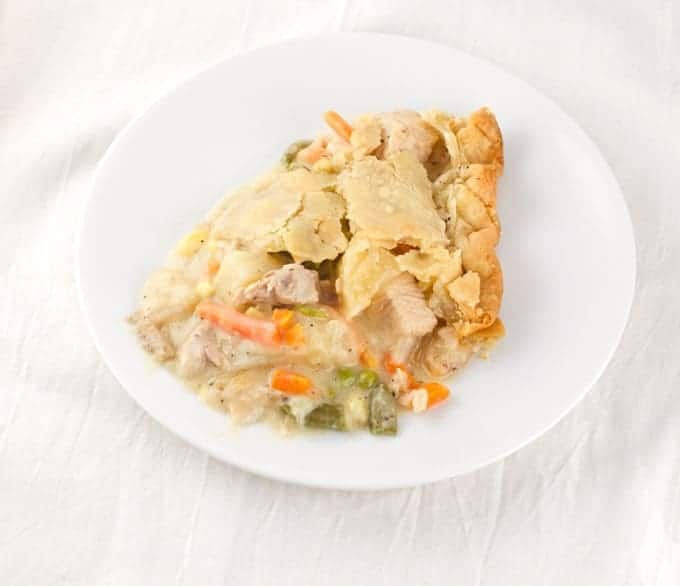 A sliced of baked chicken pet pie on a small white plate sitting on a piece of white cheesecloth as a background.
