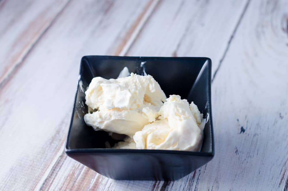 Vanilla ice cream in a black bowl on a distressed wood background