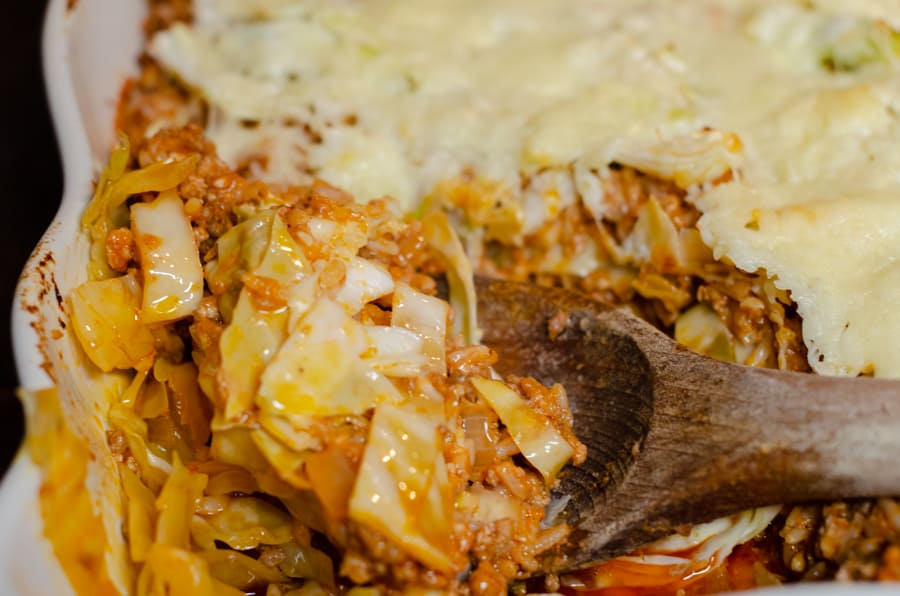 Creamy Unstuffed Cabbage Roll Casserole Recipe in casserole with a wooden spoonful being held to serve