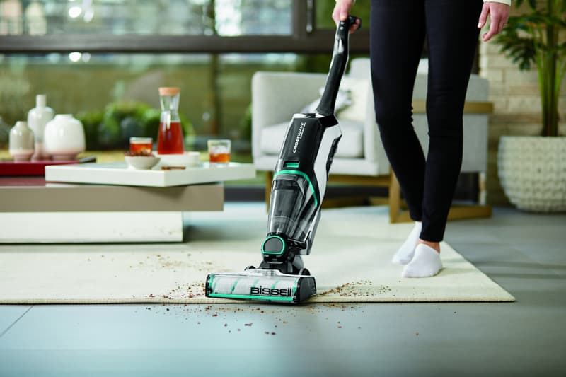 4 Reasons To Love The BISSELL CrossWave Cordless Max Multi-Surface Wet/Dry Vacuum - Vacuum is cleaning up debris on a white area rub and dark hard floor