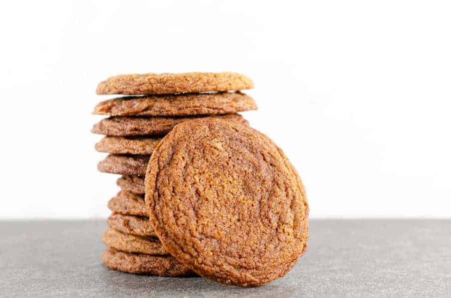 A stack of 10 crispy ginger molasses cookies with one cookie leaning up against them on a slate surface with a marble background.