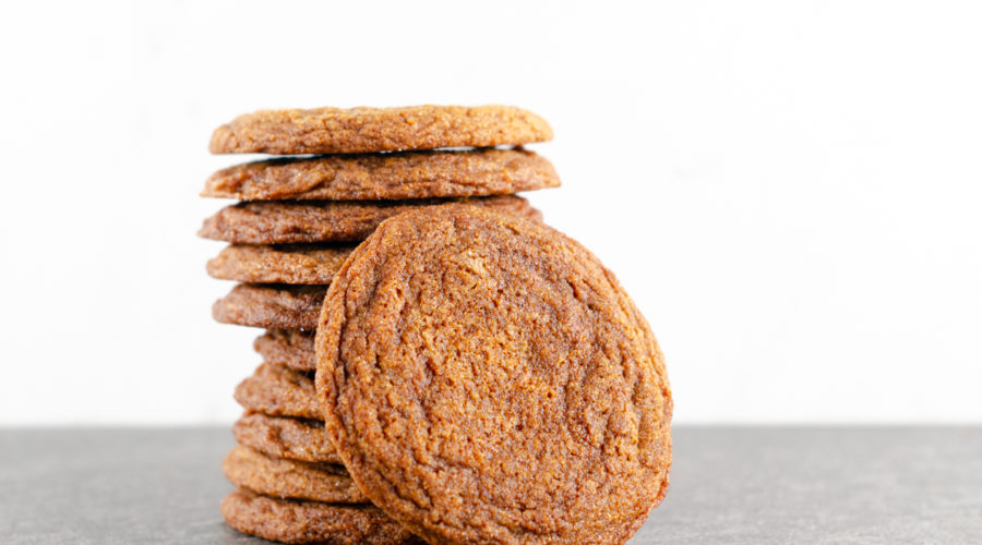 stack of 10 crispy ginger molasses cookies stacked on each other with 1 standing to the side against them