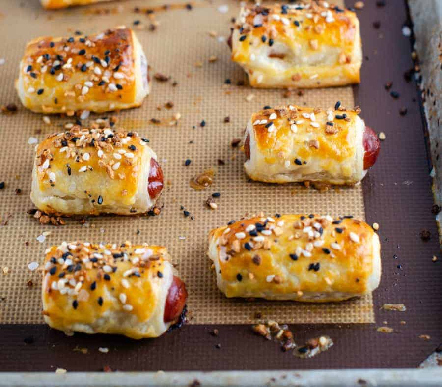 baked everything bagel pigs in a blanket sitting on a silpat on a baking sheet