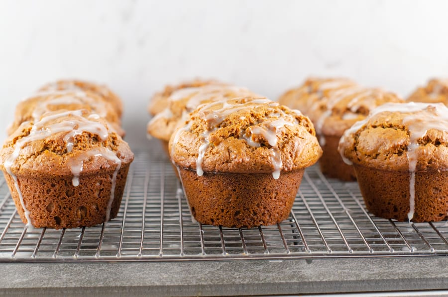 baked gingerbread muffins dripping with lemon glaze sitting on a metal cooling rack on a slate surface and marble background