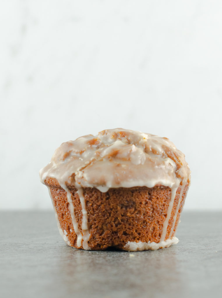 Frontal closeup of a glazed gingerbread muffin on a slate surface with marble background