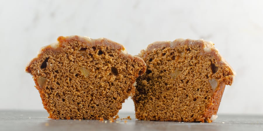 baked and glazed gingerbread muffin cut in half to see the inside with chunks of candied ginger