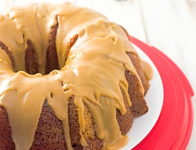 spice bundt cake with salted caramel glaze sitting on a white plate on top of a red plastic cake holder bottom