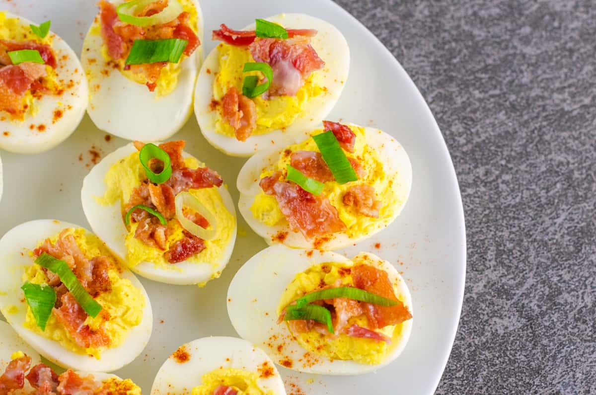 deviled eggs garnished with cayenne pepper, bacon, and sliced green onion on a white plate on a black slate countertop