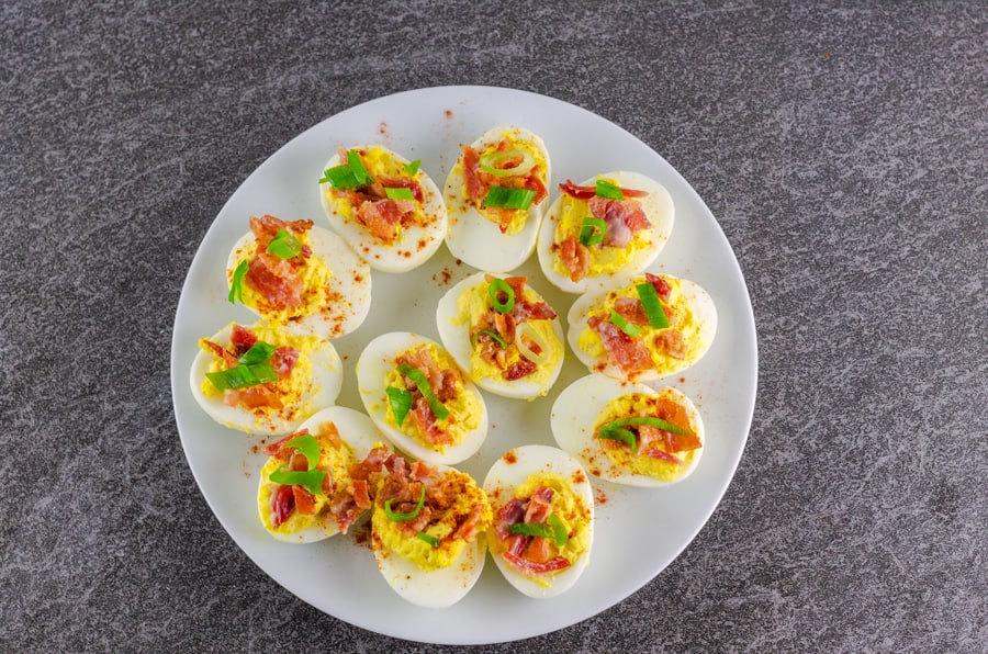 completed bacon deviled eggs garnished with cayenne, bacon, and slices of green onion on a white serving plate on top of a black slate counter top