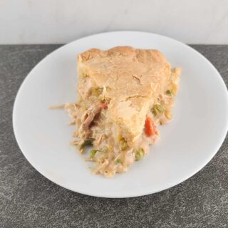 An overhead shot of a slice of baked chicken pot pie with the tip facing the front on a small white round plate on a slate surface and marble background.