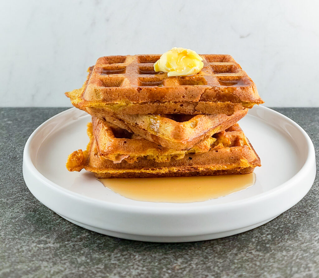 frontal view of 3 pumpkin waffles stacked on each other topped with a pat of butter and maple syrup on a shallow white plate sitting on a slate surface and marble background