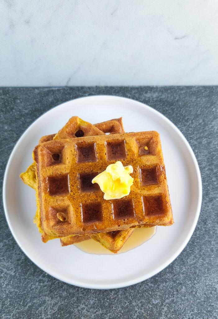 overhead shot of 3 pumpkin waffles stacked on top of each other with a pat of butter and heavy drizzle of maple syrup on a shallow round white plate on a slate surface with a marble background