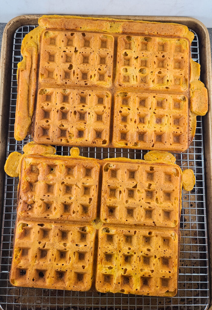 8 waffles in 2 4-waffle sheets that have been cooked and are sitting on a wire rack on a half sheet baking pan
