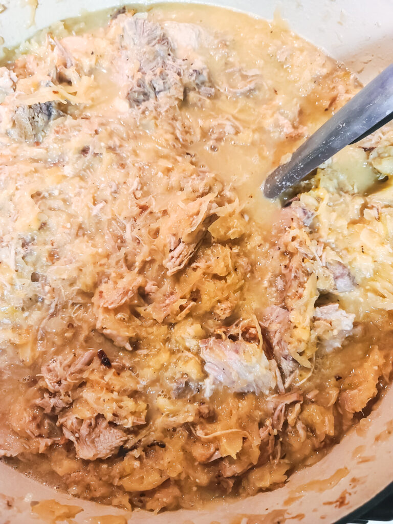 finished kraut and pork in Dutch oven ready to serve